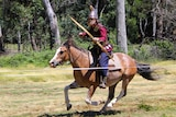 A man wearing armour and carrying a bow and arrow while riding a horse.
