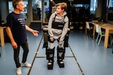 Jean-LouisConstanza stands next to his son Oscar who is standing up wearing the exoskeleton.