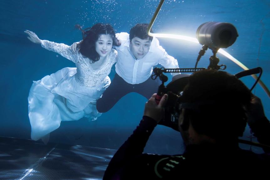A couple has their wedding photograph taken underwater.