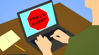"""A cartoon of a person using a laptop with the words """"fraud alert"""" in a red stop sign."""