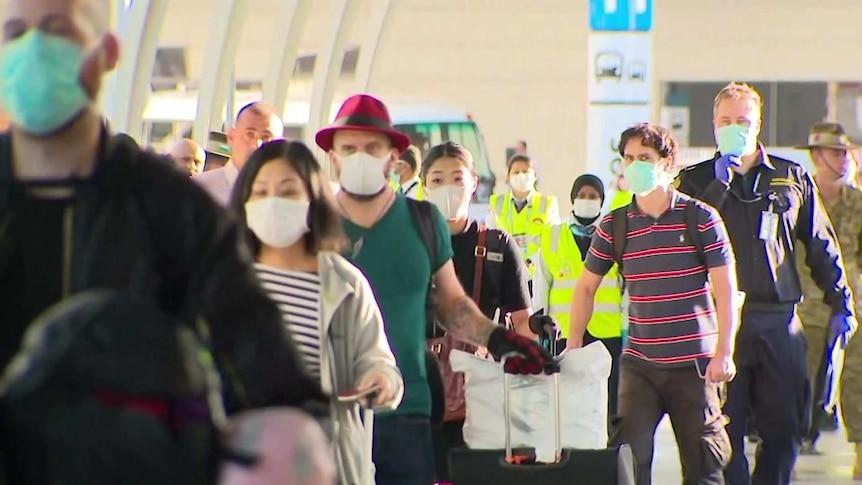 A line of passengers wearing masks.