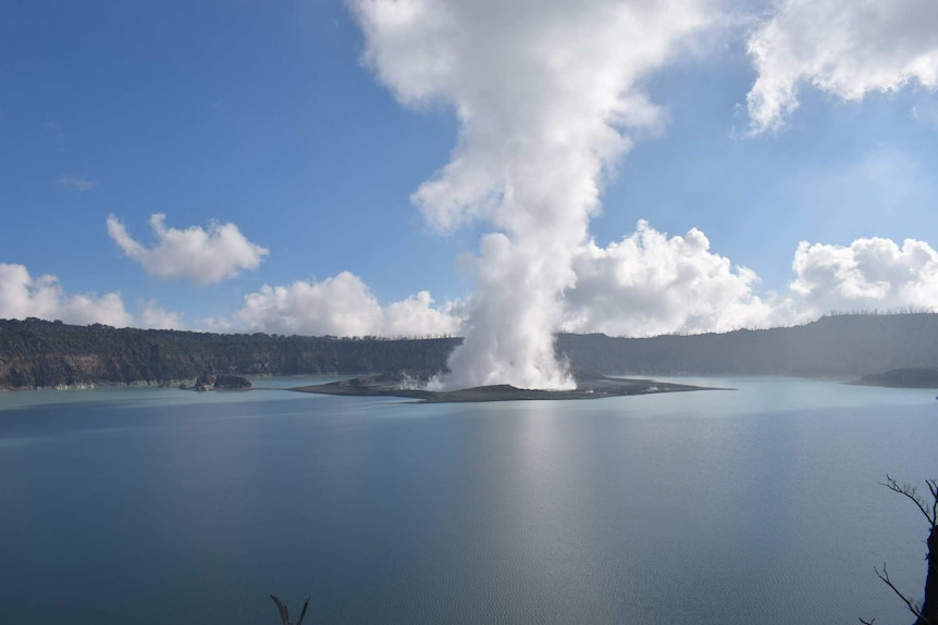 Smoke is seen coming out of Manaro volcano in the middle of a body of water.