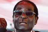 Robert Mugabe raises his fist as he speaks into microphones.