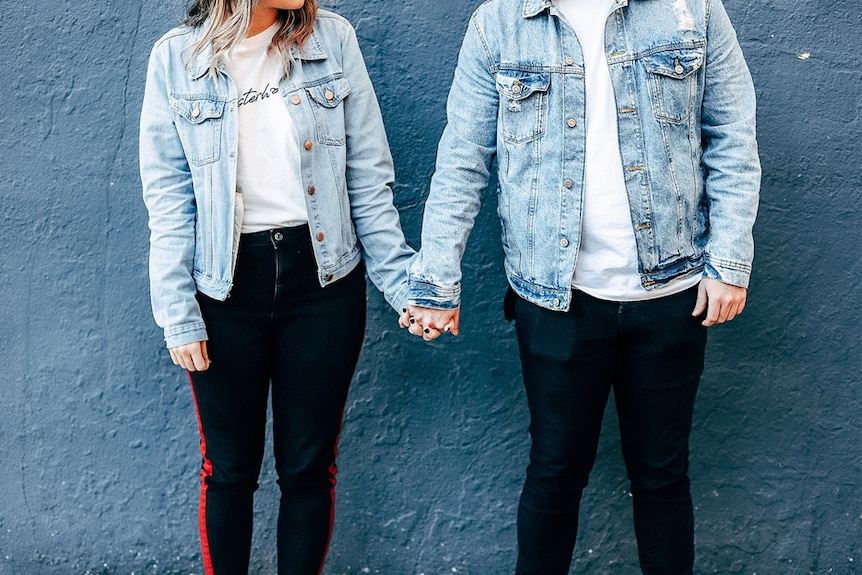 A couple wearing denim jackets holding hands