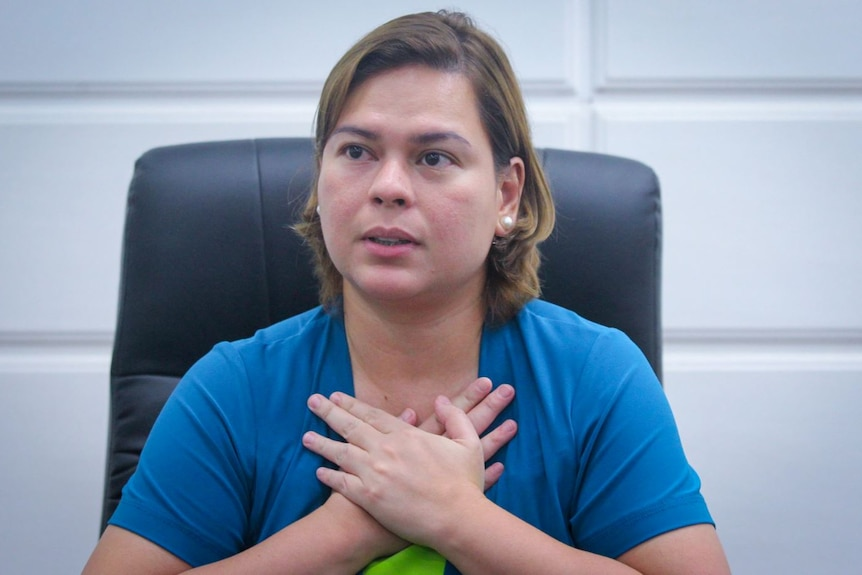 Sara Duterte with her hands folded over her chest