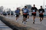 American soldiers run on a road near Baghdad.