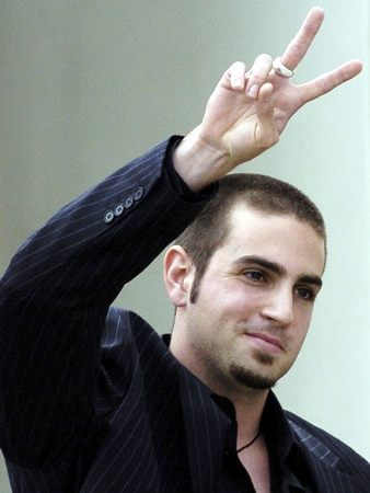 Wade Robson, as an adult, holds his hand up in a 'peace' gesture.