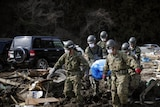 Members of Japan's self-defence force carry a body out of the rubble