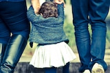 Two parents hold the hands of a toddler.