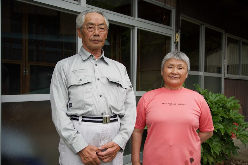 An older Japanese couple stand in front of a house