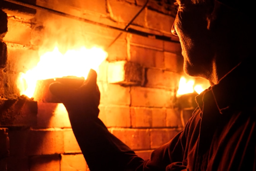 Man's face lit by fire as he pulls a brick out of a kiln and fire bursts out.