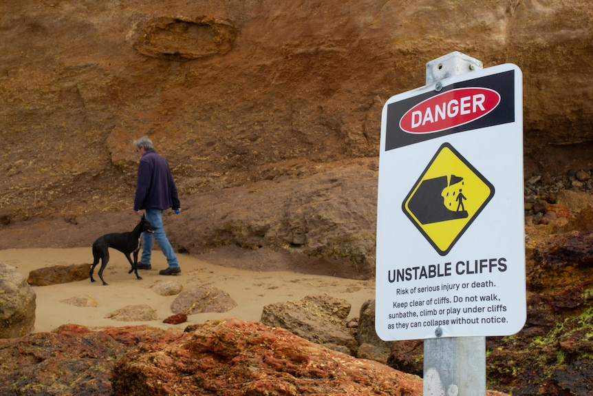 A man and his dog are walking under the cliffs with a sign next to them warning people to stay away from the cliffs due to erosion.