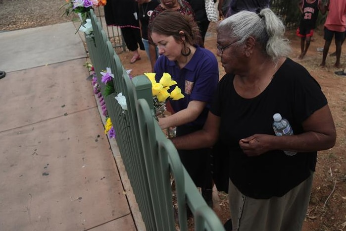 Two women put flowers on a fence as part of the vigil.