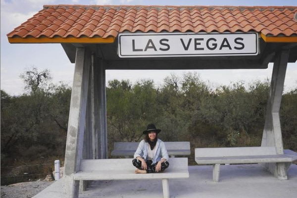 Yasmin Bright sits at a bus stop with the words Las Vegas written above it.