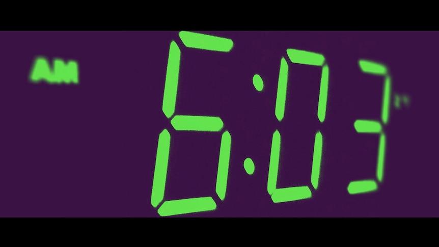 A digital clock face showing 6:03am.