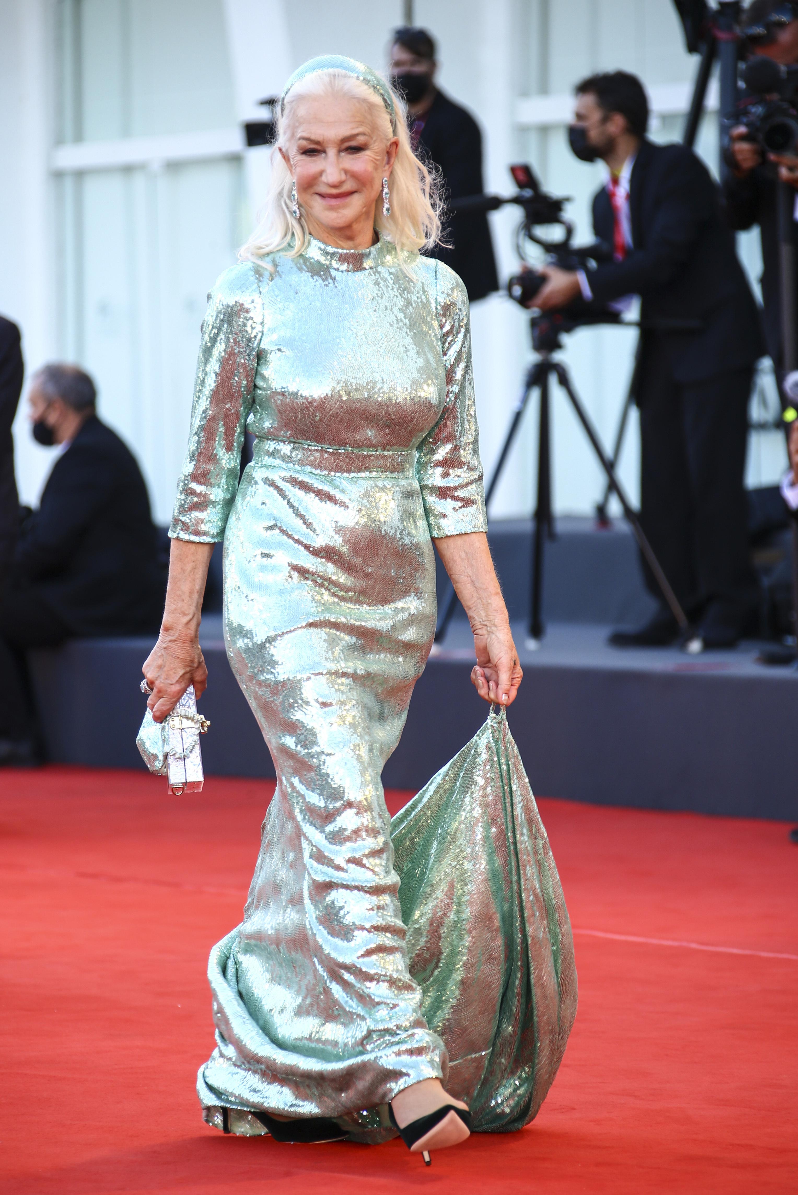 Helen Mirren indossa un abito blu metallizzato lungo fino al pavimento con maniche e fascia abbinate
