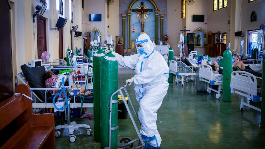 A man in full PPE moves a giant oxygen tank through a church filled with hospital beds