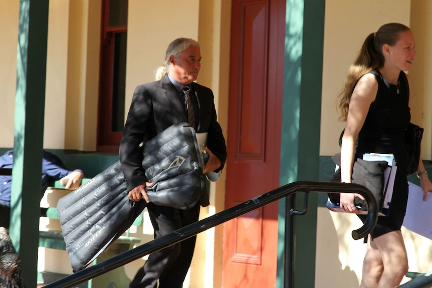 A man in a black suit with long white hair holding an inflatable mat under his arm walks to court