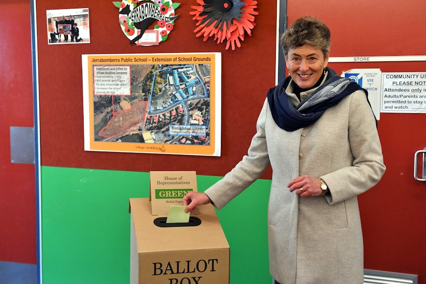A woman in a light grey jacket and a blue scarf stands beside a voting box .