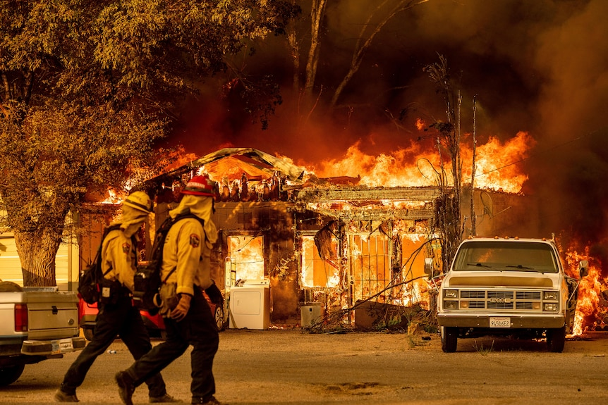 Firefighters pass a burning home