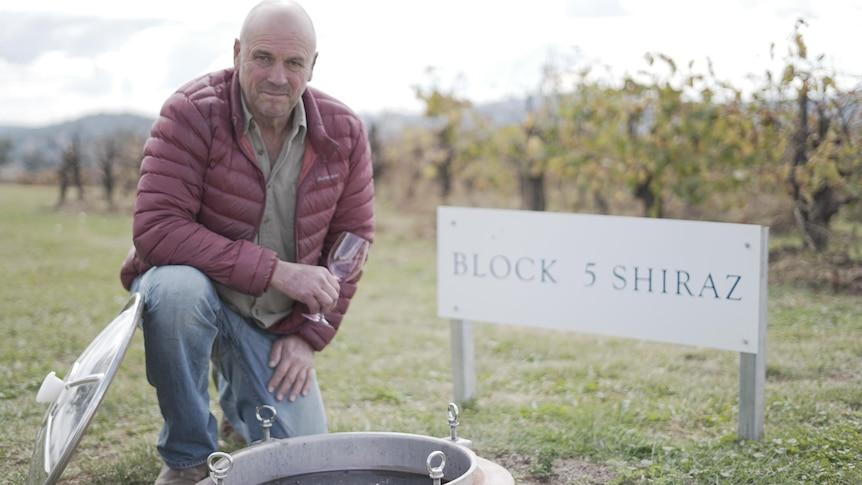 A man kneeling down in front of his vineyard