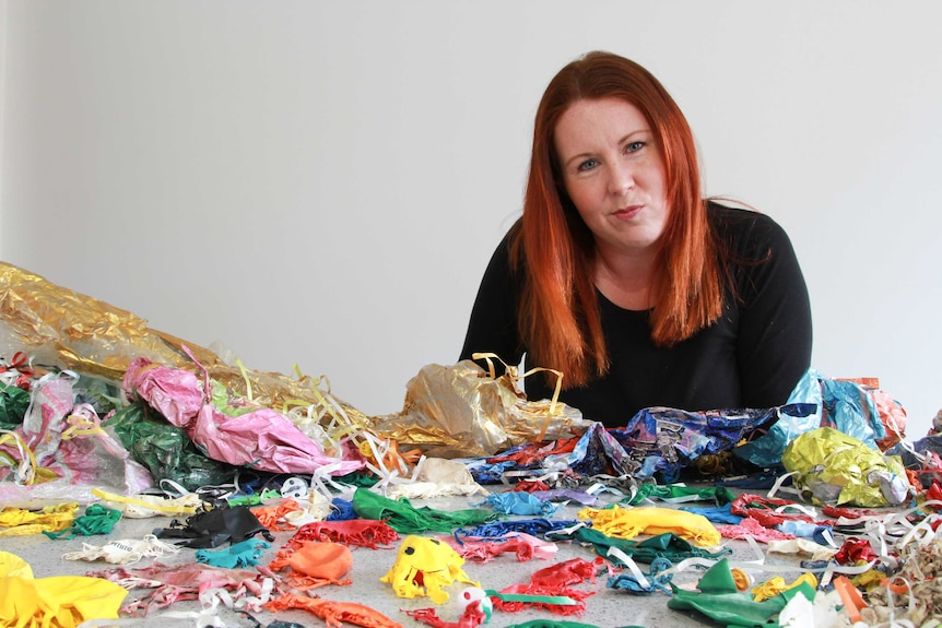 Lady sitting in front of deflated helium balloons.
