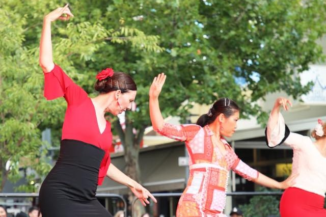 Three women perform cultural dances on stage.