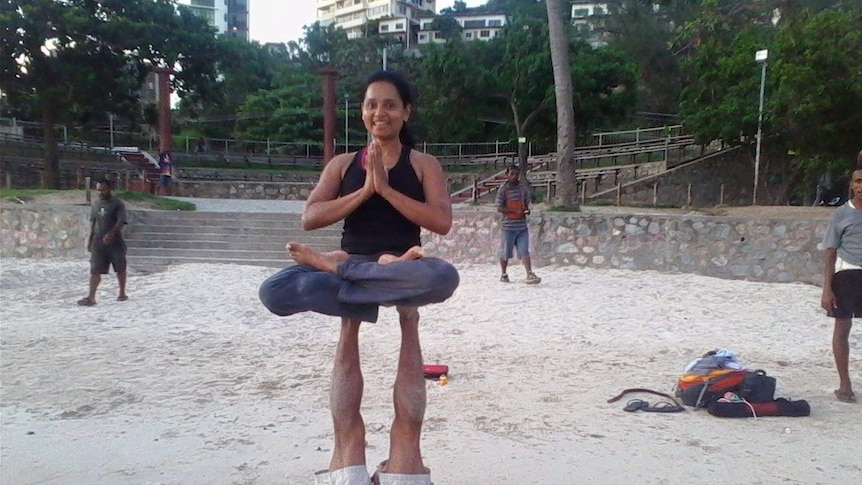Fazilah Bazari holds a yoga pose, perched atop the legs of a yoga partner