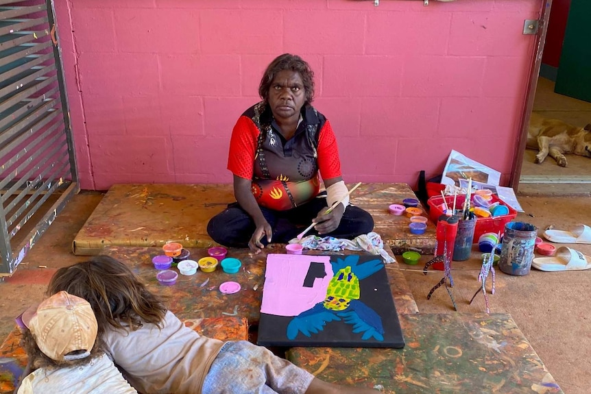 Woman sitting on ground in an art centre painting with two children lying in front of her