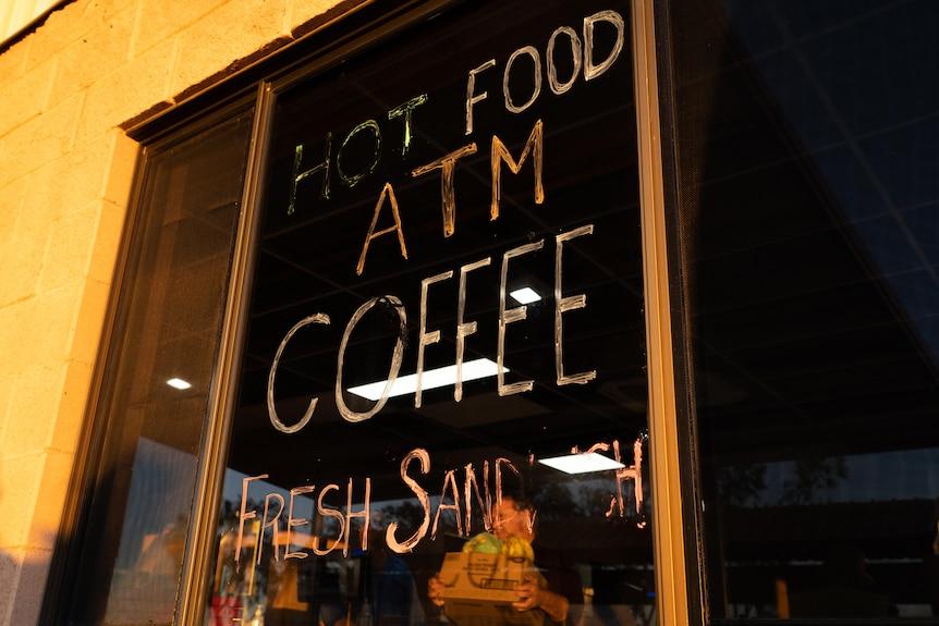 "A sign on a window says ""hot food, ATM, coffee, fresh sandwich"". Through the window a man walks with a box of fresh fruit."