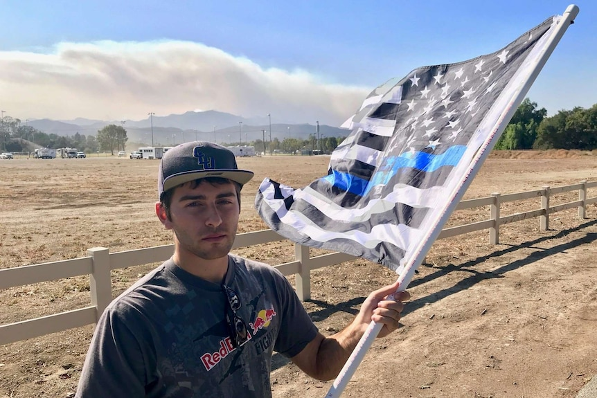 Brandon Apelian holds a black and white american flag as smoke rises in the background