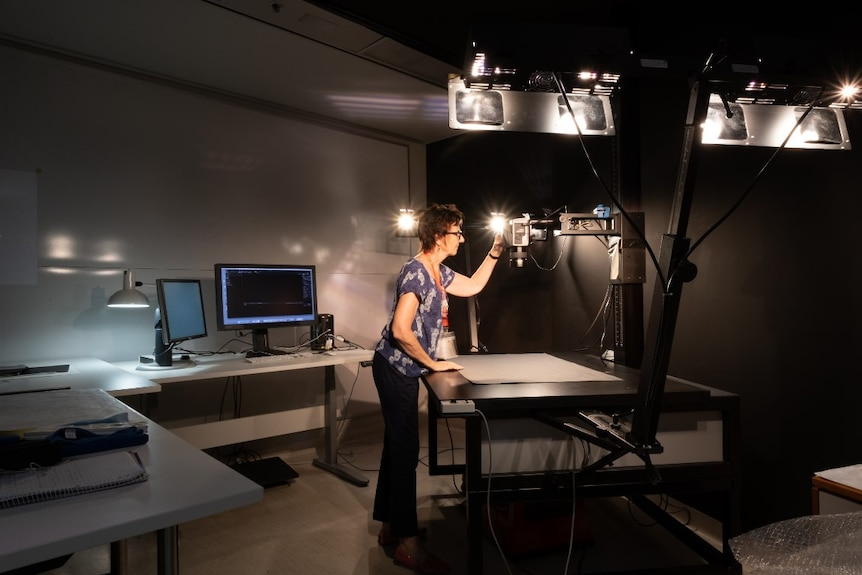 A woman sets up a digitisation station with camera and lights in a dark room