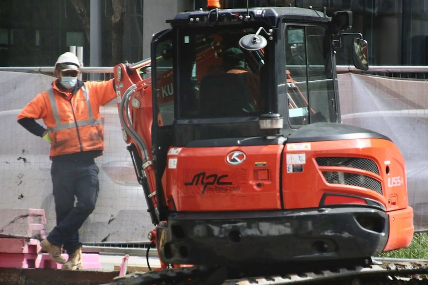 A construction worker wearing a mask, helmet and orange fluro top leans against a small excavator.