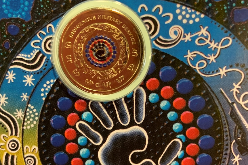 A coin, inset into an Indigenous artwork. Both the coin and the painting feature a handprint.