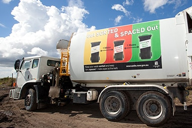 A white garbage truck with its back hatch open and a sticker on the side showing different types of rubbish bins.