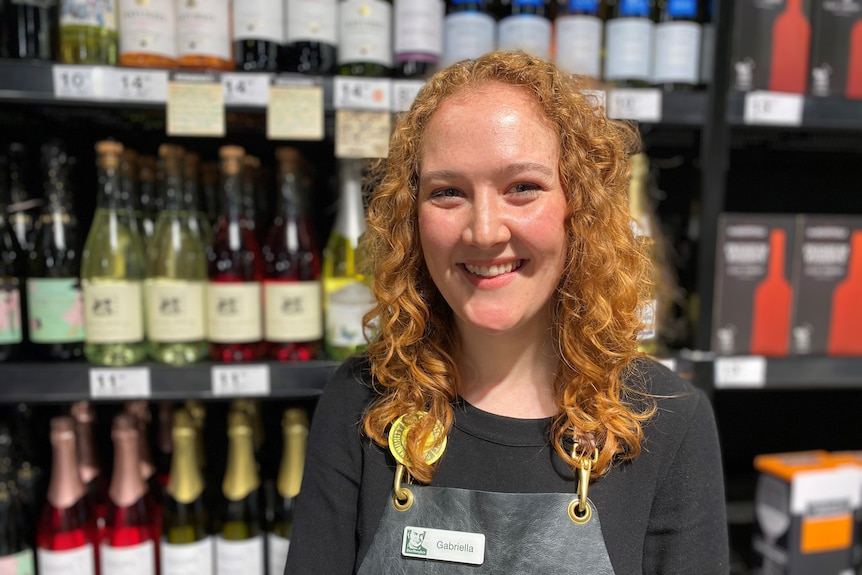 Gabriella Rush, a young woman with orange hair, smiles happily in front of a display of wine.