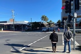 Two people walk in an unusually quiet street of Coffs Harbour