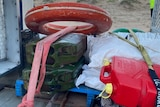 A life buoy, jerry cans and waterproof cases