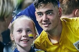 A soccer player smiles at fan taking a photo alongside a smiling young female fan