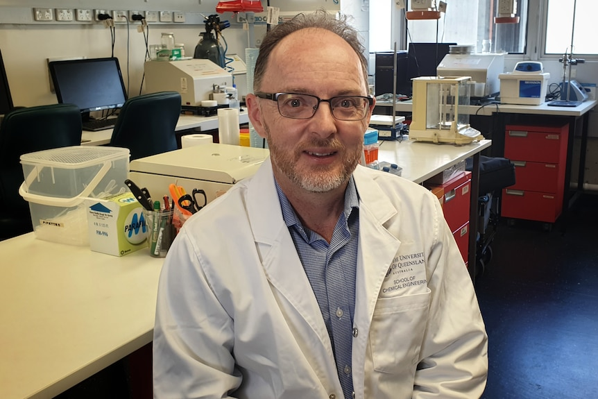 Professor Jason Stokes in a lab coat, wearing glasses, sitting and smiling, stuff behind.