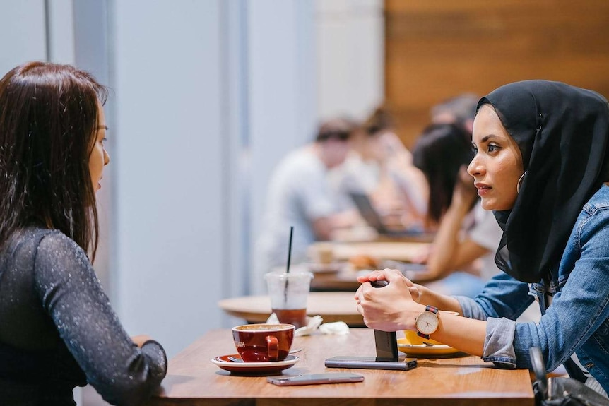 Two women sit at a table in a cafe, talking together.