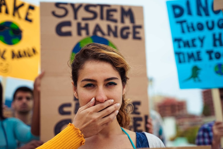 A woman with a hand over her mouth during a protest.
