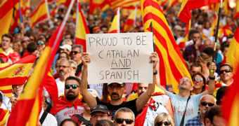 """A man holds a sign saying """"proud to be Catalan and Spanish"""", in a Catalonia protest."""