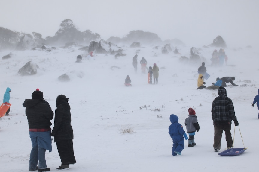 Snowy hazy day with people dressed in snow gear dragging toboggans.
