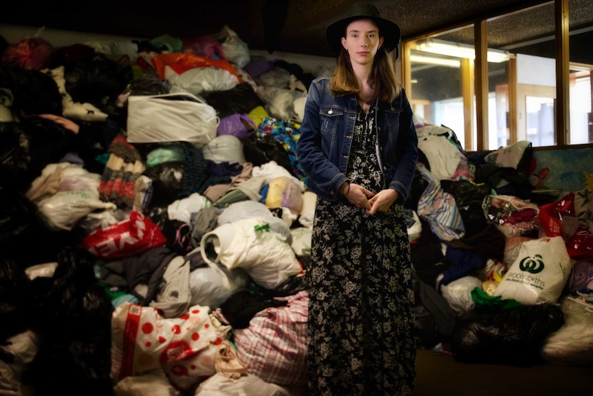 Young woman in a dress, hat and denim jacket stands in front of a large pile of op shop donations.