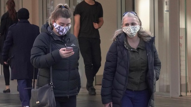 Two women wear patterned face masks while walking on a city street in winter clothes