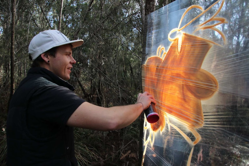 Tasmanian artist James Cowan spray painting a mural on plastic food wrap stretched between trees.