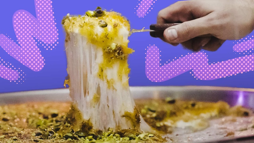 A hand pulls a piece of a cheesy dessert called knafeh from a large plate, in front of a purple background