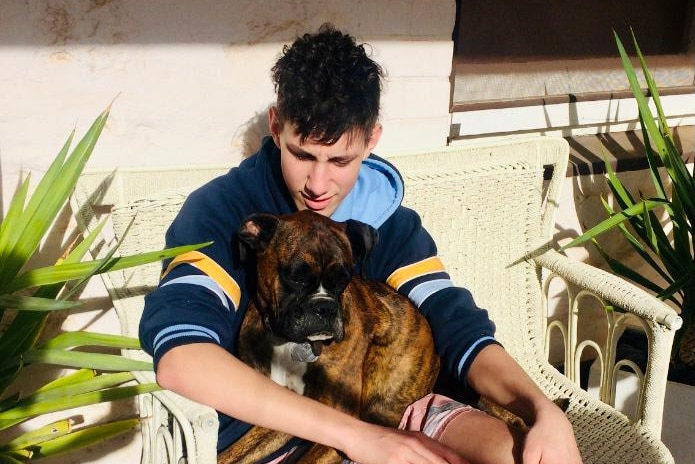 A high school student sits down with a dog on his lap.