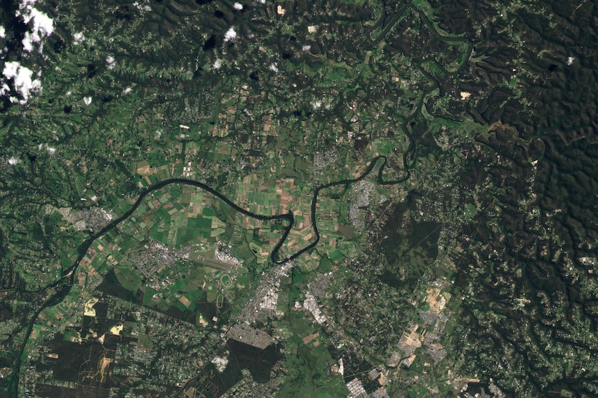 aerial view of a town and river its mostly green